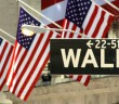 stock-footage-street-sign-american-flags-on-wall-street-new-york-city-usa