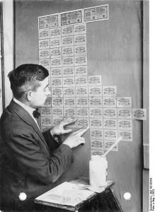 Archiwalne zdjęcie przedstawiające proces tapetowania ściany pokoju markami.