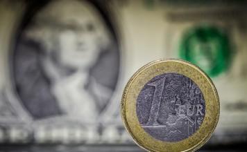 Moneta euro na tle jednego dolara