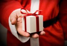 Święty Mikołaj trzymający w ręce prezent