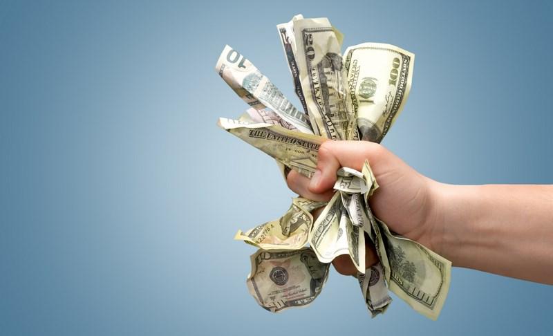 dłoń ściskająca plik dolarów