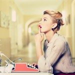 kobieta zamyślona przy maszynie do pisania