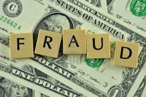 Kostki scrabble ułozone w słowo FRAUD na banknocie dolarowym