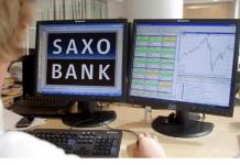 Logo Saxo Bank na jednym z monitorów. Drugi przedstawia wykresy cenowe.