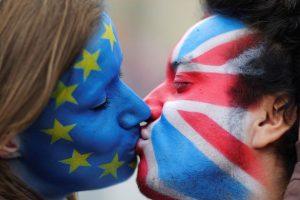 Całujące się kobiety z flagami UE i UK na twarzach