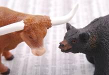 figurki byka i niedźwiedzia na tle notowań giełdowych w formie pisemnej