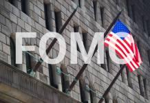 Napis FOMC na tle amerykańskiej flagi