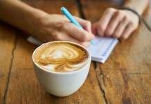 Kubek z kawą na stole, w tle notes