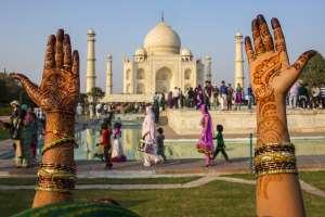 Ręce wytatuowane henną wzniesione do góry na tla Taj Mahal