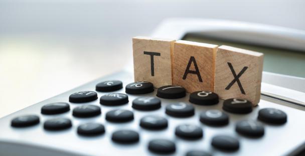Napis TAX dotyczący podatków umieszczony na kalkulatorze