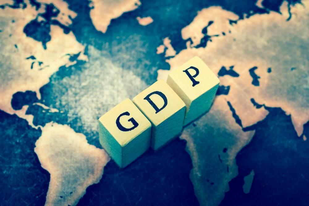 klocki z literami składającymi się w słowo GDP ustawione na mapie świata