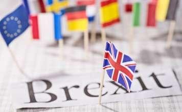 Brexit, flaga Wielkiej Brytanii UK, a w tle flagi państw europejskich