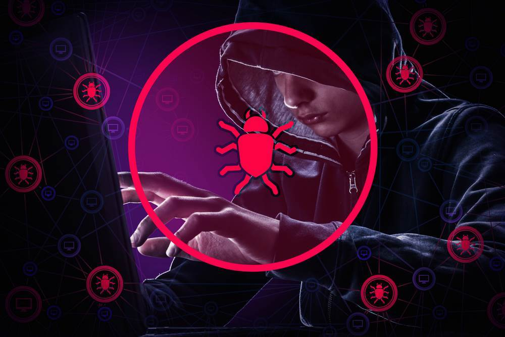 Haker w kapturze przed laptopem. Robaki / wirusy komuterowe