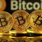 trzy złote monety Bitcoina z logiem i nazwą bitcoin w tle