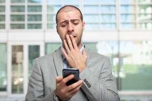 zmartwiony mężczyzna patrzy na smartfona
