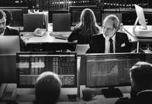 czarnobiałe zdjęcie traderów siedzących przed monitorami z wykresami