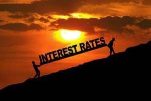 dwie osoby niosące napis interest rates pod górę na tle zachodzącego słońca