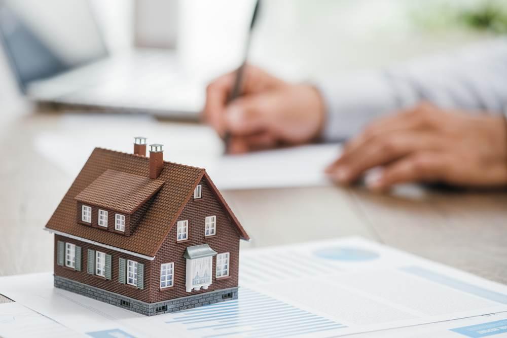 Miniatura domu stojąca na biurku, w tle mężczyzna piszący na papierze