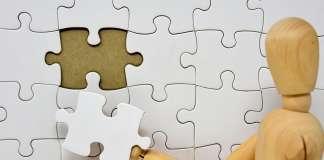 drewniany ludzik na tle puzzli