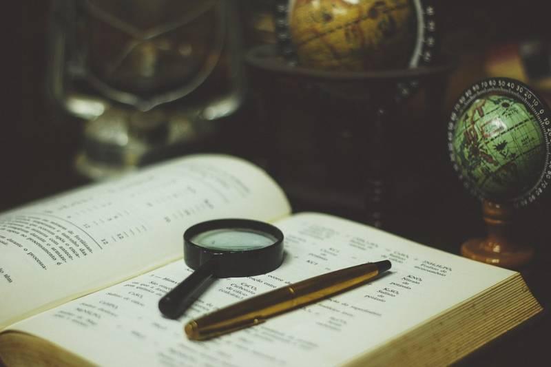 Lupa i długopis na otwartej książce