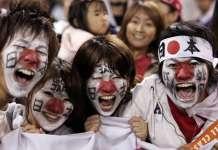 japońscy kibice z flagami na twarzach