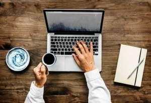 Ręce piszące na klawiaturze z kubkiem kawy
