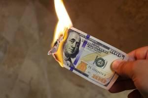 Płonący banknot trzymany w dłoni