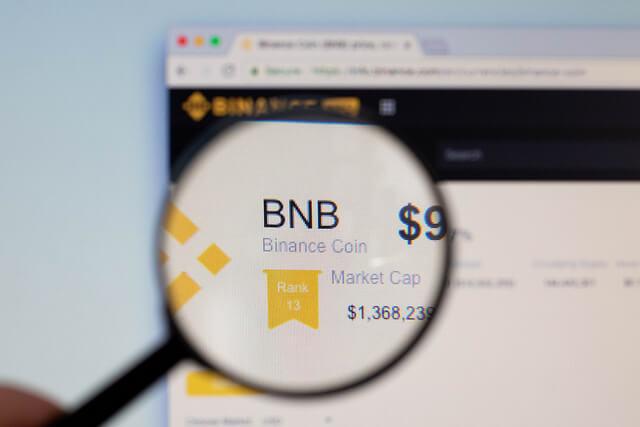 Lupa skierowana na stronę internetową z notowaniami tokena Binance Coin (BNB)