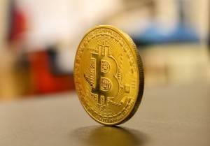 Moneta Bitcoin stojąca na krawędzi