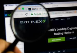 Lupa powiększająca skierowana na logo giełdy kryptowalut Bitfinex