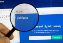 Lupa powiększająca skierowana na logo giełdy kryptowalut Coinbase