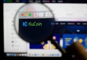 Lupa powiększająca skierowana na logo giełdy kryptowalut KuCoin