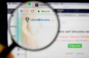 Lupa powiększająca skierowana na logo giełdy kryptowalut LocalBitcoins