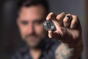 Moneta Bitcoin trzymana w dłoni przez mężczyznę
