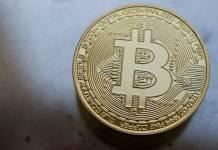 Moneta Bitcoin leżąca na stole