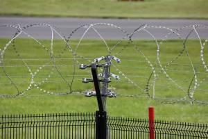 Druty więzienne na tle trawy
