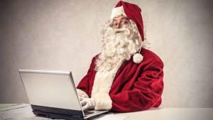 Mikołaj siedzący przy laptopie