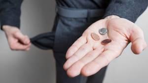 Mężczyzna trzymający się za pustą kieszeń z drobnymi na dłoni