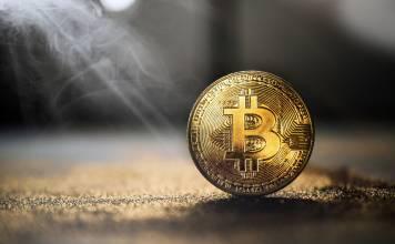 Moneta Bitcoin stojąca na stole